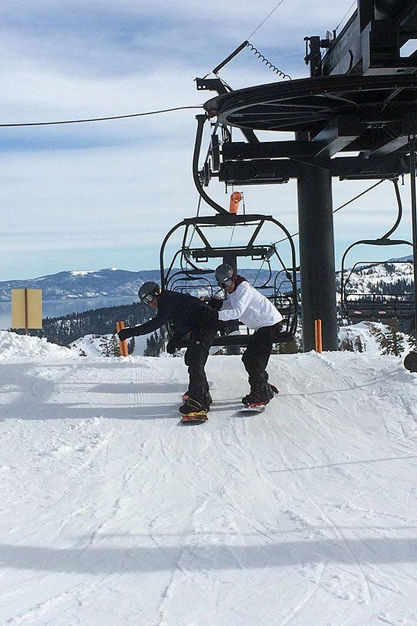 Senior Joel Castillo, dressed in black, and senior Juan Thunander, dressed in white, ride the ski lift to the top of the mountain. At the end of the lift, they attempted to get used to the snowboards but were caught off balance.