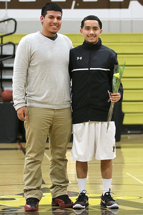 Senior Andres Andrade is escorted by senior Giovanni Gutierrez on his last basketball game against Bear Creek.