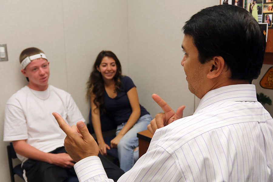 Counselor Kevin Oki, speaks to seniors Brenda Pelayo and Stephon Favella about this year's schedule.