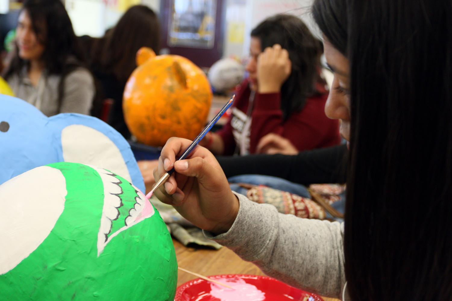 Freshmen Ivie Leyva is painting the mouth onto her paper mache character, Mike Wazowski.