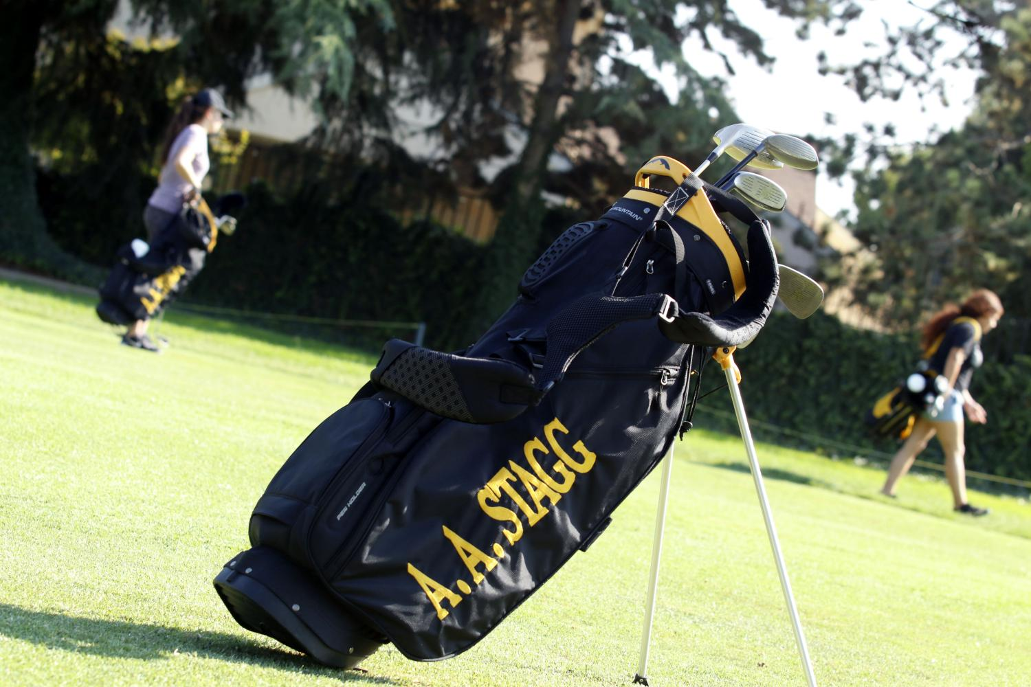 The girls carry their bags to go practice their swing.