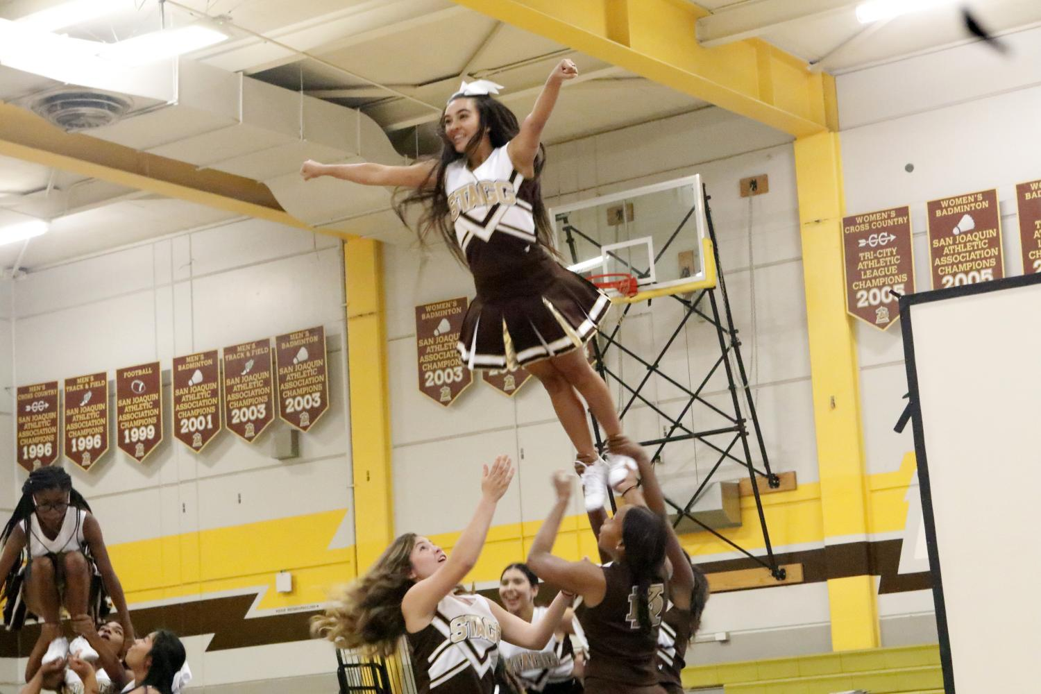 Alyzea Deputron is doing a super stunt during the cheer performance.