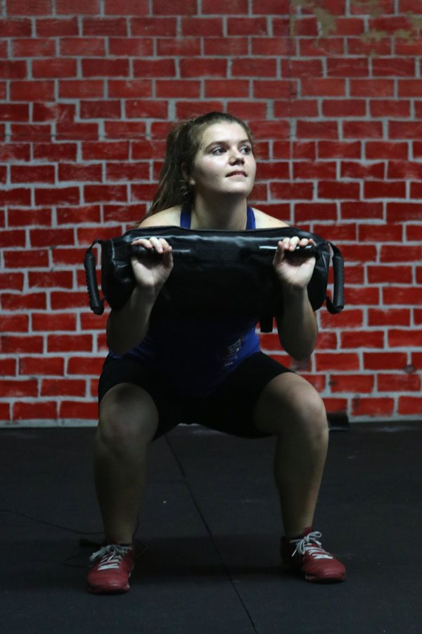 Savannah Iske, freshman, performs a deep squat while keeping her head up to try to maintain an appropriate back posture. Iske lifts a 40 pound weight bag.
