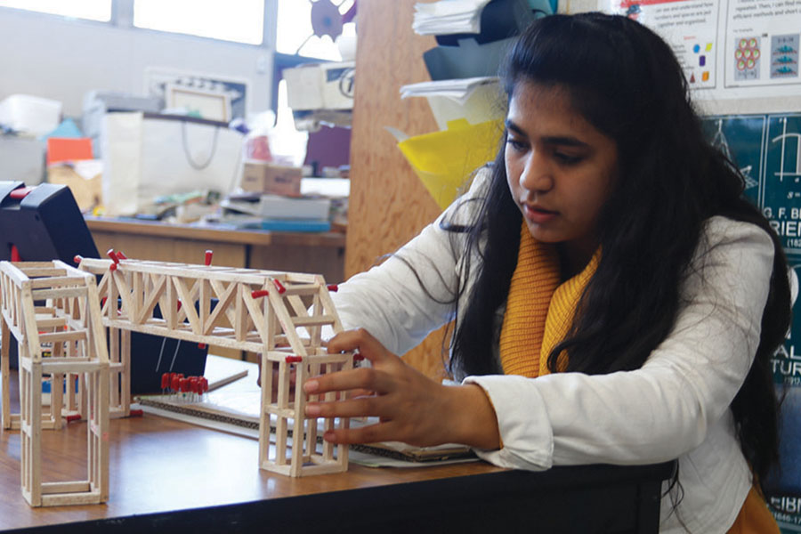 Sophomore Maha Kamran works on her bridge during MESA's build night, where students could stay as late as 6:30 to work on their projects for that weekend's MESA Day competition.