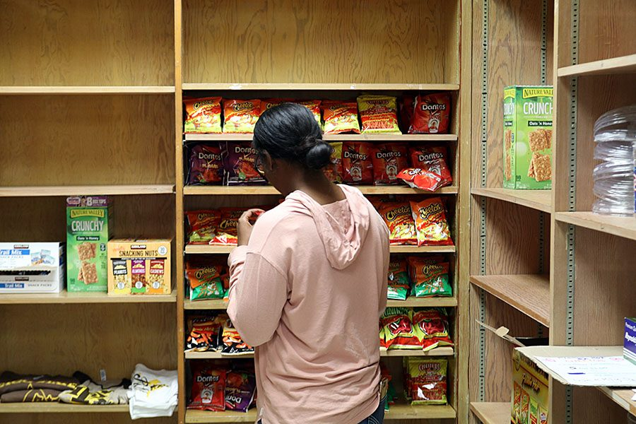 ASB member Senior, Natalie ONeil casually stocks the chips on to the shelf of the Student Store.