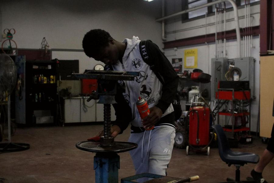 Lawson is oiling down a piece of equipment that will go beneath the car engine.