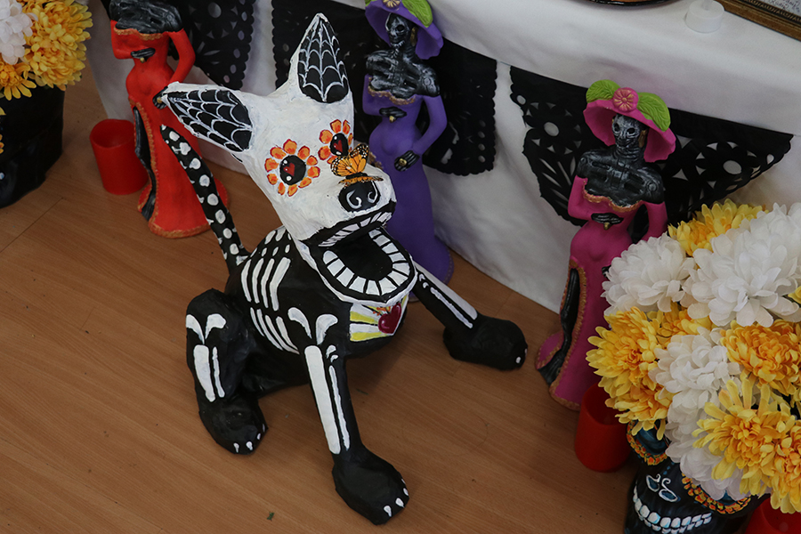 A+dog+version+of+the+%22sugar+skulls%27+made+of+paper+mache+sits+in+front+of+a+shrine.+