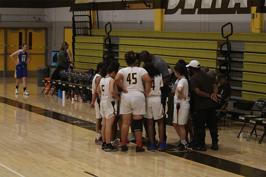 Varsity girls basketball team gathers with their coach Finis Jones to go over some plays before their game.