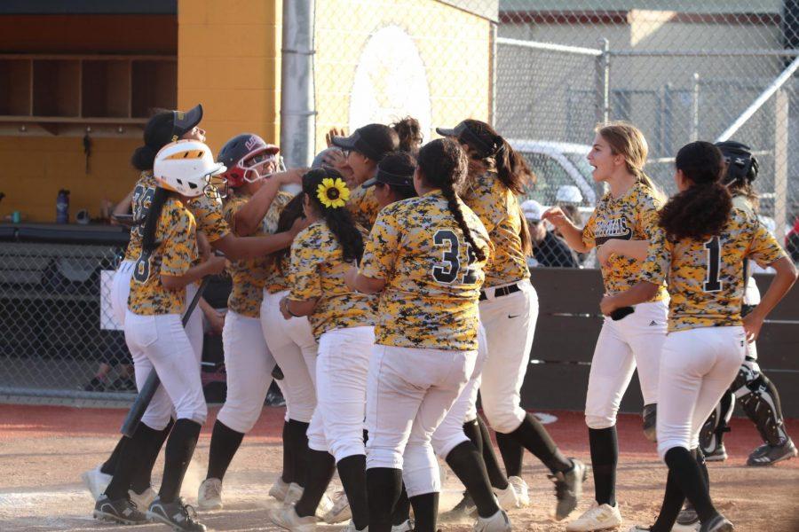 Delta queens swarm their fellow queen Brianna Rodriguez after she hits a home run.