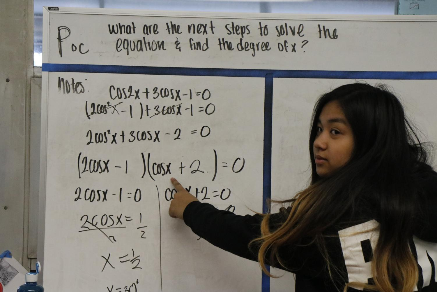 Senior Alyssa Nueno presents a question to her collaborative study group in AVID. She points out the correct steps it takes to solve the equation and where she was confused at first.