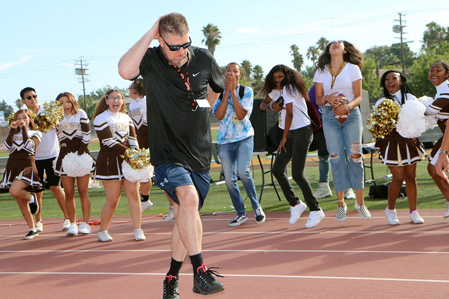 Mr. Dawson busting a move while students cheer him on.